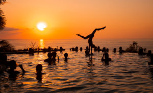 Young woman, young women, young men, acrobatics, infinity pool, swimming pool, sunset, sun, pool party, silhouette, sea, Central America, Costa Rica