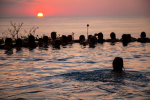 Young woman swims in infinity pool, pool party, sunset, sun, silhouette, ocean, young women, young men, Central America, Costa Rica