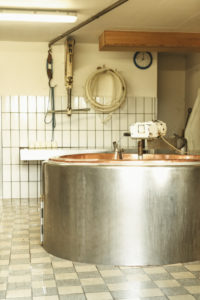 dairymaid porcesses fresh milk to aromatic alp cheese, report, hat and cleaning of the required tools and utensils,