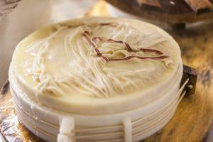 Die Sennerin verarbeitet frische Milch zu würzigem Alm-Käse, Reportage, Die geschnittene Milch wird in eine Form gefüllt und zu einem Laib weiterverarbeitet,