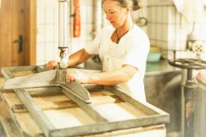 Die Sennerin verarbeitet frische Milch zu würzigem Alm-Käse, Reportage, Die geschnittene Milch wird gepresst und zu einem Laib weiterverarbeitet,