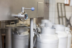 Die Sennerin verarbeitet frische Milch zu würzigem Alm-Käse, Reinigung der für die Käseproduktion benötigen Gegenstände, Abfüllanlage