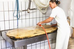 Die Sennerin verarbeitet frische Milch zu würzigem Alm-Käse,  Reinigung der für die Käseproduktion benötigen Gegenstände,