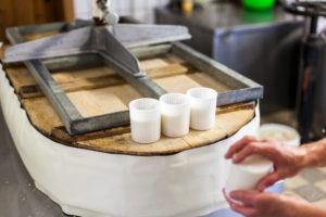 Die Sennerin verarbeitet frische Milch zu Frischkäse, der Käsebruch wird in Förmchen gefüllt und weiterverarbeitet,
