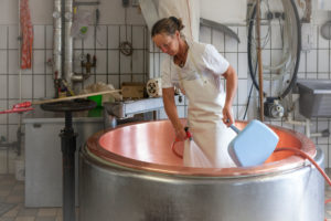 dairymaid porcesses fresh milk to aromatic alp cheese, The milk pot is cleaned carefully, 'Kesseltanz',