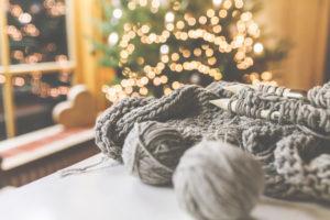 Gemütliches Weihnachten mit schöner Beleuchtung und dem Strickzeug mit großen Nadeln und schöner Wolle.