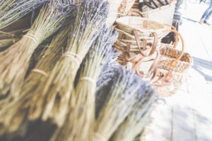 Baskets and bundles of dried lavender at a market stall.