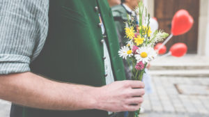 A man in a traditional shirt and vest is holding a small bouquet of flowers to congratulate him on the wedding.