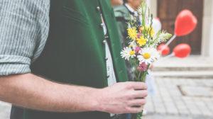 Ein Mann mit Trachtenhemd und Weste hält einen kleinen Blumenstrauß in der Hand, um zur Hochzeit zu gratulieren.