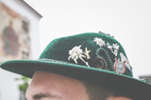 The head of a man with a Bavarian traditional hat and individual badges and lucky charms on it.