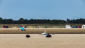 Frau mit Bikini und  Sonnenhut liegt im Sand und sonnt sich, St.Peter Ording, Strandurlaub