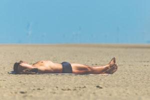 Mann mit Badehose liegt im Sand und sonnt sich, St.Peter Ording, Strandurlaub, im Hintergrund Windräder
