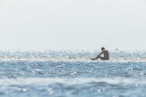 Mann mit Badehose sitzt im Wasser im Wattenmeer und beobachtet die Wellen und die kommende Flut.
