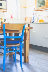 Innenansicht - ein blauer Stuhl,  ein Holztisch in einer kleinen Küche in einem Haus.