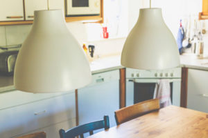 Innenansicht - zwei Lampen, Tisch und Stühle in einer kleinen Küche in einem Haus.