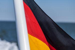 Eine deutsche Fahne, im Wind wehend, auf einem Schiff am Meer. Schwarz, Rot, Gold die Nationalfarben. Symbolbild