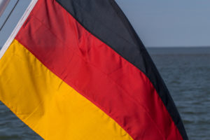 A German flag, waving in the wind, on a ship by the sea. Black, red, gold are the national colors. Icon image