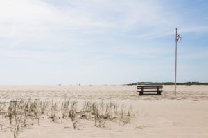 Eine Bank lädt zum Sitzen ein. Amrum, eine Insel in der deutschen Nordsee - Sand soweit das Auge reicht. Wittdün