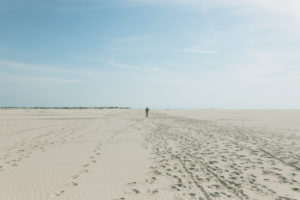 A man walks through the sand. Amrum, an island in the German North Sea - sand as far as the eye can see. Wittdün