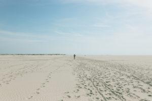 Ein Mann geht durch den Sand. Amrum, eine Insel in der deutschen Nordsee - Sand soweit das Auge reicht. Wittdün