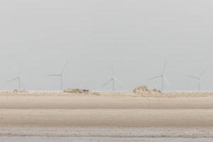 Fata Morgana am Wattenmeer - Flirrendes Licht - Blick über den Strand am Wattenmeer zu den Windrädern am Horizont.