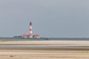 Fata Morgana - in der Ferne steht der Leuchtturm Westerheversand - Wandern und Weitsicht im norddeutschen Wattenmeer.