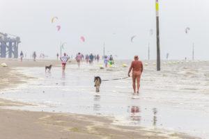Ein Mann geht nackt  mit seinem Hund am Strand spazieren