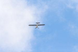 Ein kleines Flugzeug, eine Propellermaschine von unten im Landeanflug.