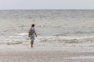 Erholung bei jedem Wetter: eine Frau watet durch das Wasser und genießt Meer und Nordsee.