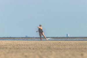 Woman in swimsuit dances, plays and enjoys the water on the Wadden Sea - detached