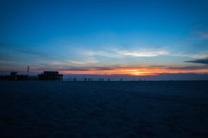 Relaxation on the Wadden Sea and on the beach of St. Peter Ording, North Sea at sunset, pile dwelling in the background