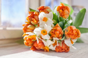 a bouquet of tulips and daffodils on a windowsill