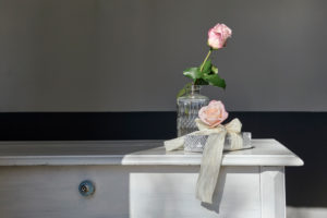 Two roses on white dresser with a gift