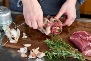 Serienmotiv, Arbeitsschritte zur Zubereitung einer mit Kräuter gefüllten Lammkeule und provenzalischem Gemüse mit einer Küchenmaschine (Thermomix ® und Varoma ®), Schnüren der Lammkeule