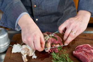 Photo series, step-by-step preparation of a leg of lamb filled with herbs and Provençal vegetables by using a food processor (Thermomix ® and Varoma ®), trussing the leg of lamb