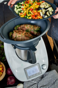 Photo series, step-by-step preparation of a leg of lamb filled with herbs and Provençal vegetables by using a food processor (Thermomix ® and Varoma ®), setting the matching tray filled with vegetables on top of the Varoma ® where the leg of lamb has been placed