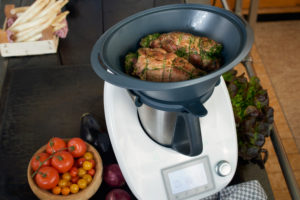 Photo series, step-by-step preparation of a leg of lamb filled with herbs and Provençal vegetables by using a food processor (Thermomix ® and Varoma ®), placing the leg of lamb in the Varoma ®