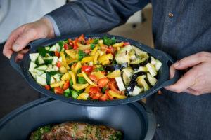 Serienmotiv, Arbeitsschritte zur Zubereitung einer mit Kräuter gefüllten Lammkeule und provenzalischem Gemüse mit einer Küchenmaschine (Thermomix ® und Varoma ®), Einsetzen des Garaufsatzes mit Gemüse über der Lammkeule