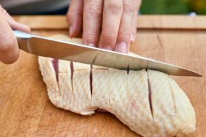 Woman's hands with chef's knife carve the skin of a duck breast on a wooden board