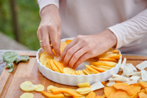 Prepare a gratin of potatoes, pumpkin and Jerusalem artichoke, arrange the sliced ingredients in a buttered baking pan