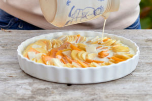 Prepare a gratin of potatoes, pumpkin and Jerusalem artichokes, pour the sliced ingredients in a buttered baking pan with milk and cream from a jug