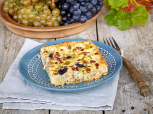 Quiche with grapes and leek, blue country plate on linen cloth, grapes in bowl, fork with wooden handle, table with untreated table top