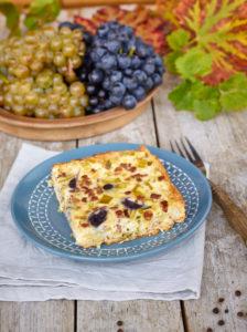 Quiche mit Trauben und Lauch, blauer ländlicher Teller auf Leinentuch, Weintrauben in Schale, Gabel mit Holzgriff, Tisch mit unbehandelter Tischplatte