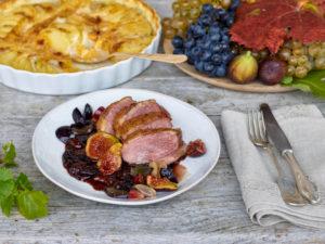 Entenbrust mit Trauben-Feigensoße, Gratin von Kartoffeln, Kürbis und Topinambur, Weintrauben und Feigen, Silberbesteck, Tisch mit unbehandelter Tischplatte