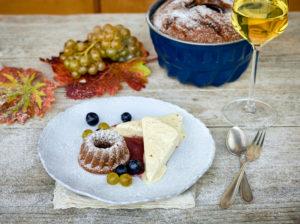 Süsswein-Parfait mit kleinem Guglhupf und Weinbeeren auf weißem Teller, Weissweinglas gefüllt und Backform, Tisch mit unbehandelter Tischplatte