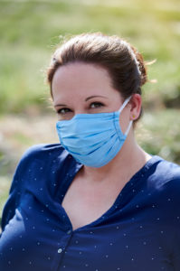 Woman with self-made face mask in nature by the river