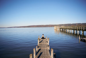 Meditation at the Ammersee, woman sitting on jetty, blue sky