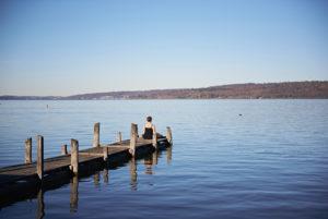 Meditation am Ammersee, Frau sitzt auf Steg, blauer Himmel