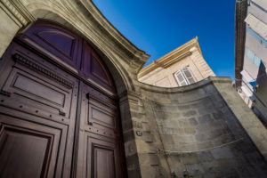 Large wooden door in the old town centre of Beziers in summer