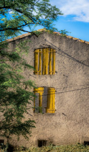 Old house with yellow shutters in Montady at Beziers